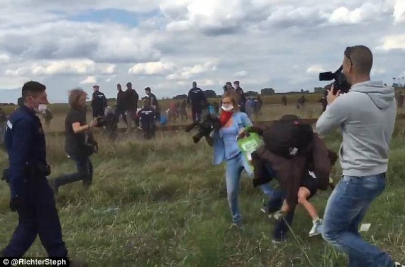 Astonishing moment a Hungarian camerawoman deliberately TRIPPED refugees who were fleeing police