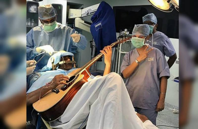 Indian musician plays guitar during brain surgery