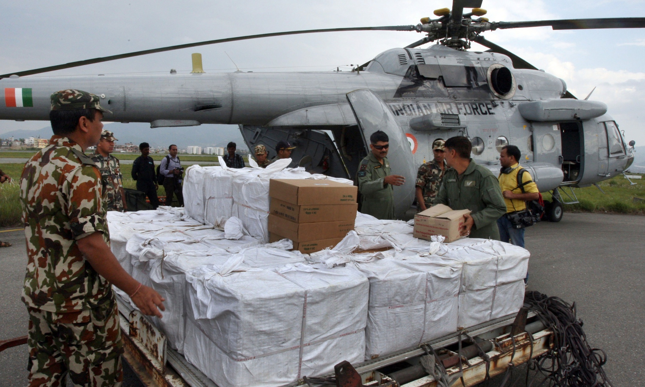 TO GO WITH Nepal-quake-India-China-diplomacy,FOCUS by Annie BANERJI and Abhaya SRIVASTAVA In this handout photo received from the Indian Air Force (IAF) on April 29, 2015 and taken on April 28, 2015, Nepalese Army personnel load relief material into an Indian Air Force MI-17 helicopter at Kathmandu airport. Nepal's overwhelmed government has been criticised by frustrated residents, hundreds of thousands of whom are desperate for assistance after the April 25 monster quake. But foreign countries, with their medics, specialist rescuers and helicopter sorties, have won applause, with giant neighbour India sometimes singled out for praise as the biggest provider. AFP PHOTO / IAF -EDITORS NOTE- RESTRICTED TO EDITORIAL USE - MANDATORY CREDIT -