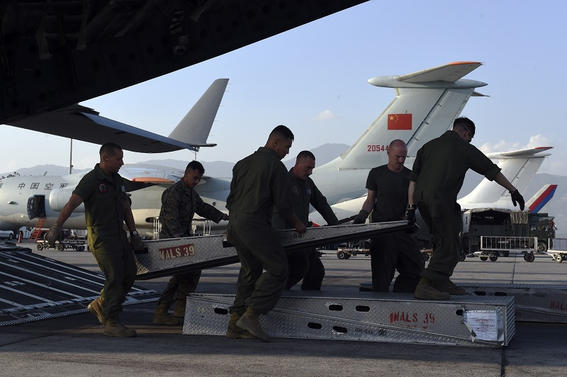 Crew members of a US military C-17 cargo plane get ready to unload a Huey helicopter they transported to Kathmandu's international airport on May 3, 2015. International aid continues to pour into Nepal to help victims of a massive earthquake on April 25 killed at least 7,200 people and devastated vast swathes of one of Asia's poorest countries. Military transport planes from China (C) and Russia (2R) can be seen in the background. AFP PHOTO/ROBERTO SCHMIDT