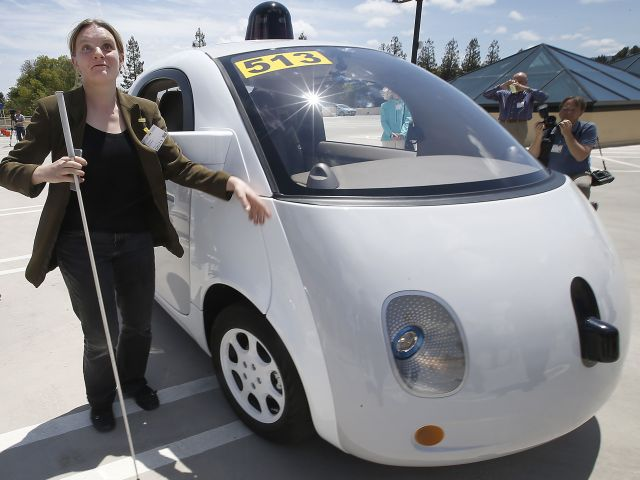 In this May 13, 2015 photo, Jessie Lorenz, of San Francisco, touches the new Google self-driving prototype car during a demonstration at the Google campus in Mountain View, Calif. The car, which needs no gas pedal or steering wheel, will make its debut on public roads this summer. (AP Photo/Tony Avelar)
