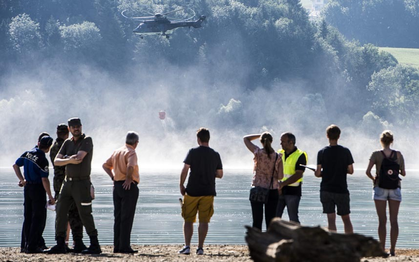 epa04858282 A Super Puma helicopter of the Swiss Army is filling a water tank above lake de la Gruyere in front of represents of the army, police, civil defense, firefighters and a group of journaliste to refill the parched cattle watering tank on the Alps of Canton Fribourg in Morlon, Switzerland, 24, July 2015. Due to the heatwave and the subsequent drought, the cattle watering tanks are empty. The farmes get help by a Swiss Army helicopter to soak their livestock. The Swiss Army helps the Canton Fribourg to manage the consequences of the heat wave. The Swiss Army has started to build up water points to supply the cattle with water. EPA/DOMINIC STEINMANN