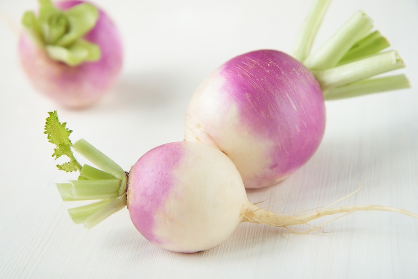Three turnips with purple skin on table