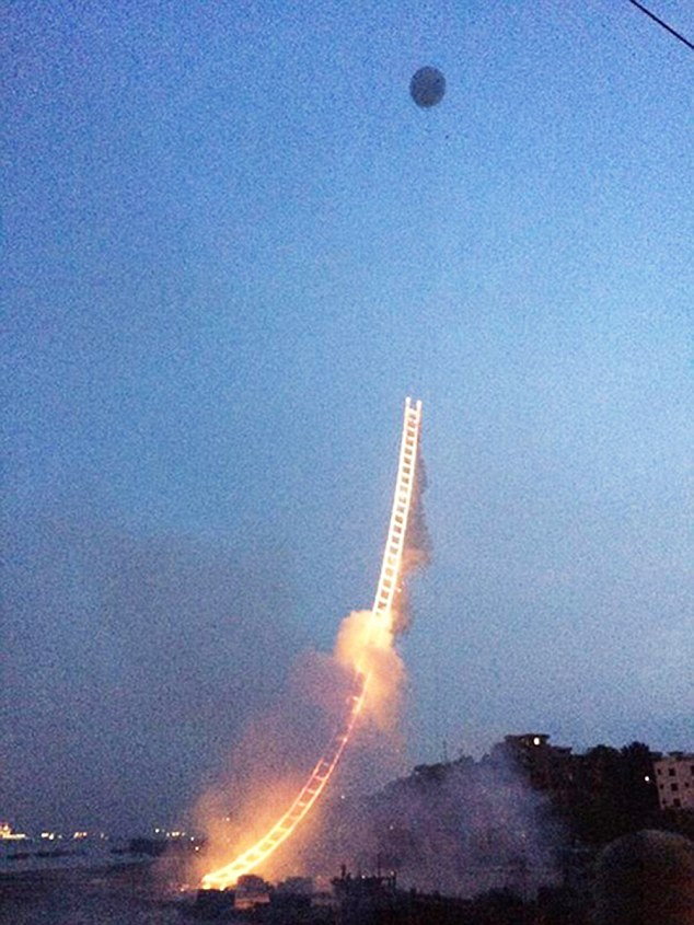 Pic shows: The firework display fullfiled by a Chinese artist in the shape of a ladder that extends up into the sky. A well-known Chinese artist and pyrotechnic enthusiast this week fulfilled his decades-old dream of creating a firework display in the shape of a ladder that extends up into the sky. Cai Guoqiang, a native Quanzhou City of south-east China's Fujian Province, put on display the art piece known as the