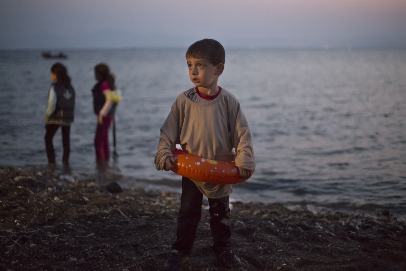 A Syrian migrant boy still wearing a swimming ring stands on the beach upon his arrival with other migrants by a dinghy at the southeastern Greek island of Kos, Greece, early Thursday, Aug. 20, 2015. Greece this year has been overwhelmed by record numbers of migrants arriving on its eastern Aegean islands, with more than 160,000 landing so far.(AP Photo/Alexander Zemlianichenko) ORG XMIT: XAZ102
