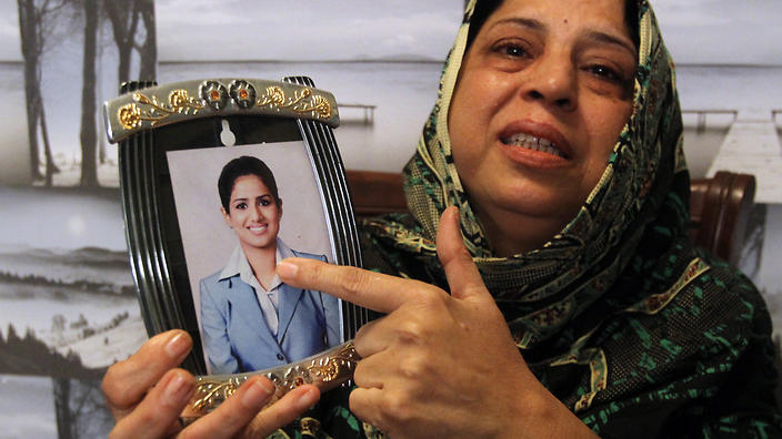 Pakistani mother, Sarwari Begum, shows a picture of her daughter, Bushra Khalique, 27, who is reportedly missing after a crush during the Hajj pilgrimage in Saudi Arabia, Saturday, Sept. 26, 2015 in Karachi, Pakistan. As the hajj religious pilgrimage entered its final day Saturday, officials in Saudi Arabia continued to grapple with the aftermath of a deadly stampede that killed at least 750 people. (AP Photo/Fareed Khan)