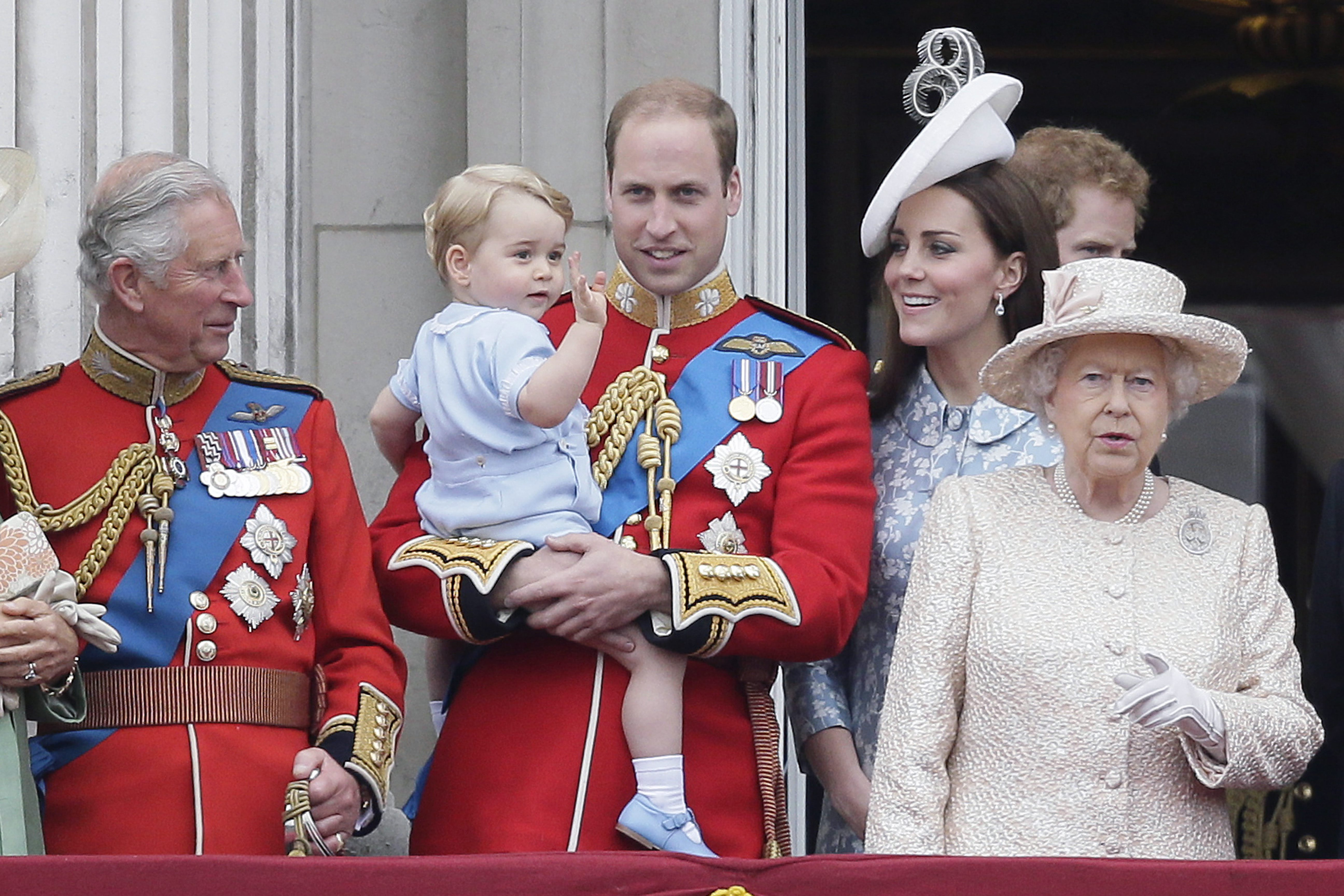 Britain's Prince William holds his son Prince George, with Queen Elizabeth II, right, Kate, Duchess of Cambridge and the Prince of Wales during the Trooping The Colour parade at Buckingham Palace, in London, Saturday, June 13, 2015. Hundreds of soldiers in ceremonial dress have marched in London in the annual Trooping the Color parade to mark the official birthday of Queen Elizabeth II. The Trooping the Color tradition originates from preparations for battle, when flags were carried or