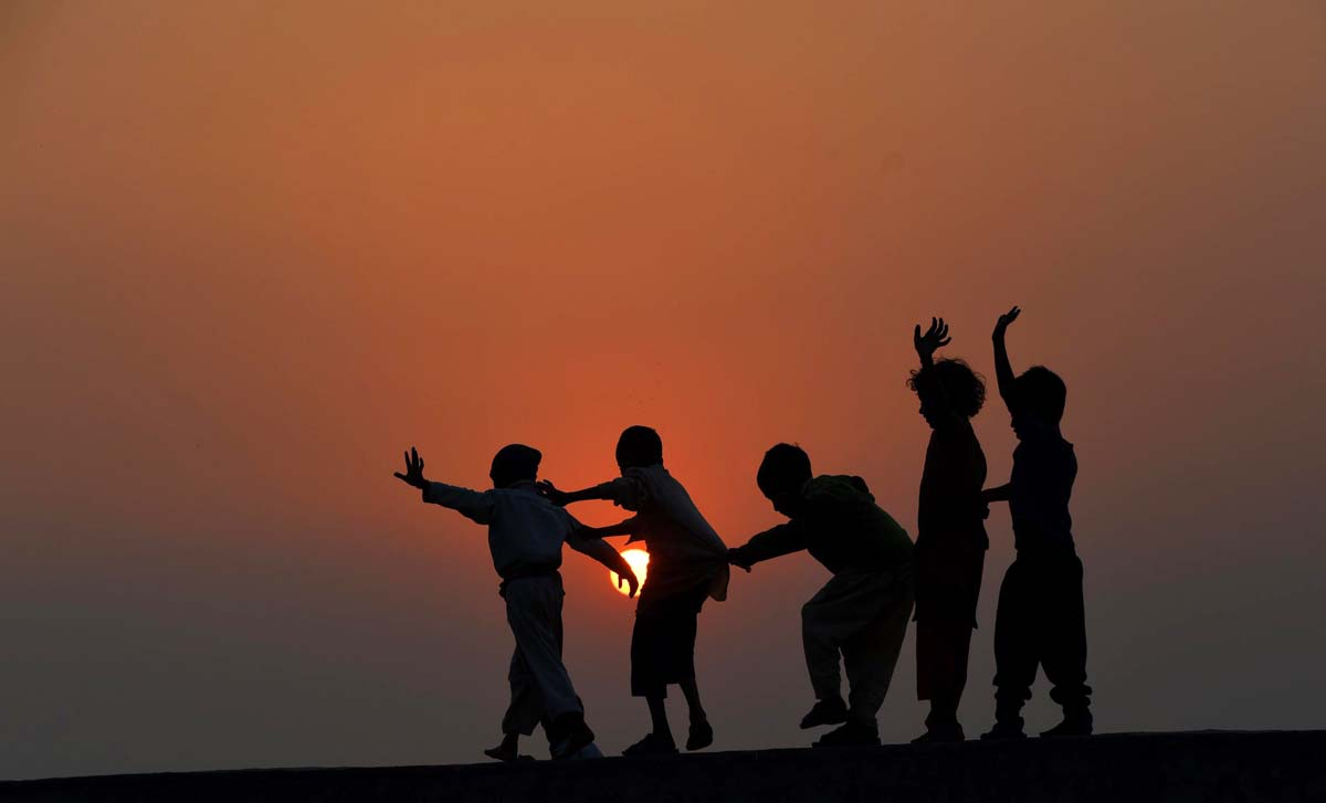 TOPSHOTS Pakistani children play on the roof of a house on the outskirts of Lahore on November 19, 2014. The United Nations' Universal Children's Day is celebrated annually on November 20 to promote worldwide fraternity and understanding between children. AFP PHOTO/Arif ALIArif Ali/AFP/Getty Images ORG XMIT: