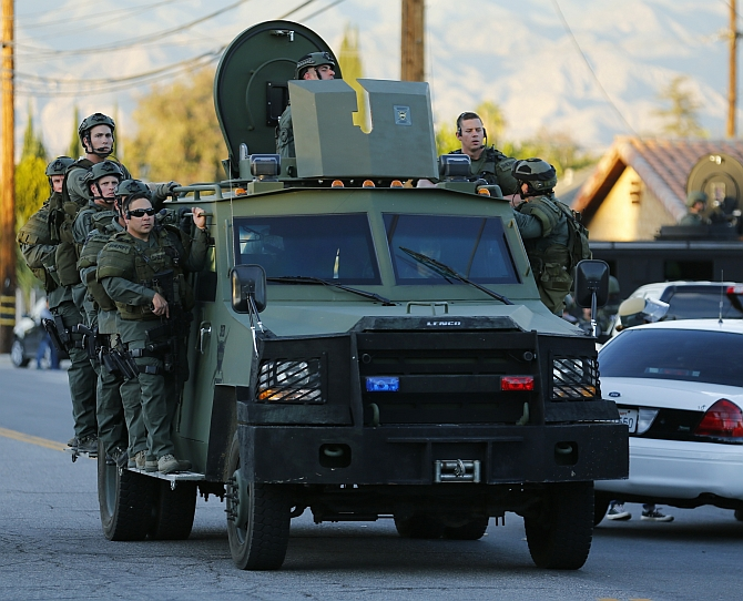 Police officers conduct a manhunt after a mass shooting in San Bernardino, California December 2, 2015. Gunmen opened fire on a holiday party on Wednesday at a social services agency in San Bernardino, California, killing 14 people and wounding 17 others, then fled the scene, triggering an intense manhunt and a shootoutout with police, authorities said. REUTERS/Mike Blake - RTX1WX4C