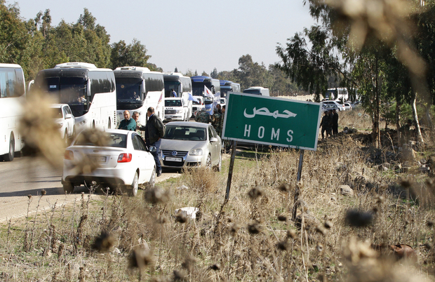 Buses evacuate Syrian civilians as hundreds of civilians and rebel forces began leaving the last opposition-held district of Waer, in the central city of Homs, under a deal with the Syrian regime, on December 9, 2015. According to Talal Barazi, Homs governor, some 700 people -- including 400 women and children and 300 fighters -- would be evacuated from the district, after a deal reached earlier this month between rebel forces and Syrian President Bashar al-Assad's regime. / AFP / LOUAI BESHARA