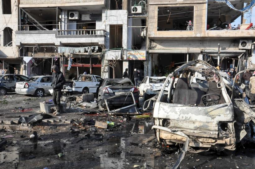 People inspect the site of a double bomb attack in the government-controlled city of Homs, Syria, in this handout picture provided by SANA on January 26, 2016. REUTERS/SANA/Handout via Reuters