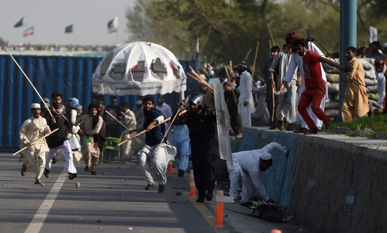 Pakistani Frontier Constabulary officials run from supporters of executed Islamist Mumtaz Qadri during an anti-government rally in Islamabad on March 27, 2016. Pakistani police fired tear gas at thousands of stone-throwing supporters of an Islamist assassin, a month after he was hanged for killing a provincial governor for alleged blasphemy. / AFP / FAROOQ NAEEM