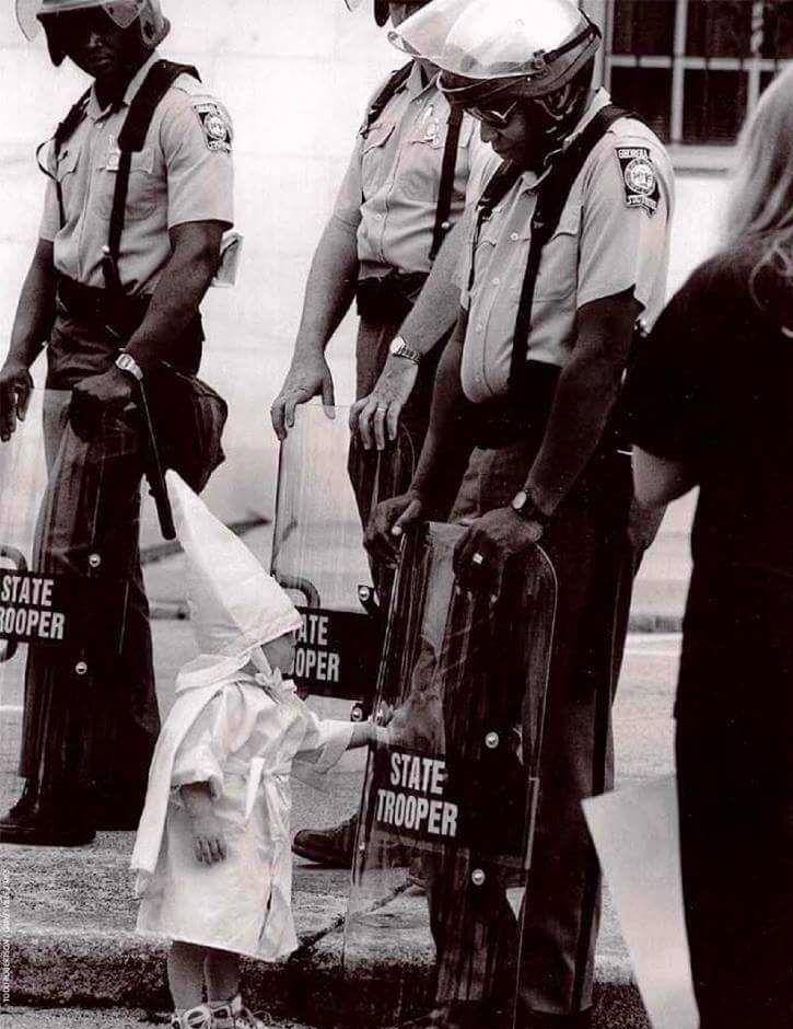 a-small-child-in-a-klan-outfit-greets-a-black-state-trooper-photo-u1