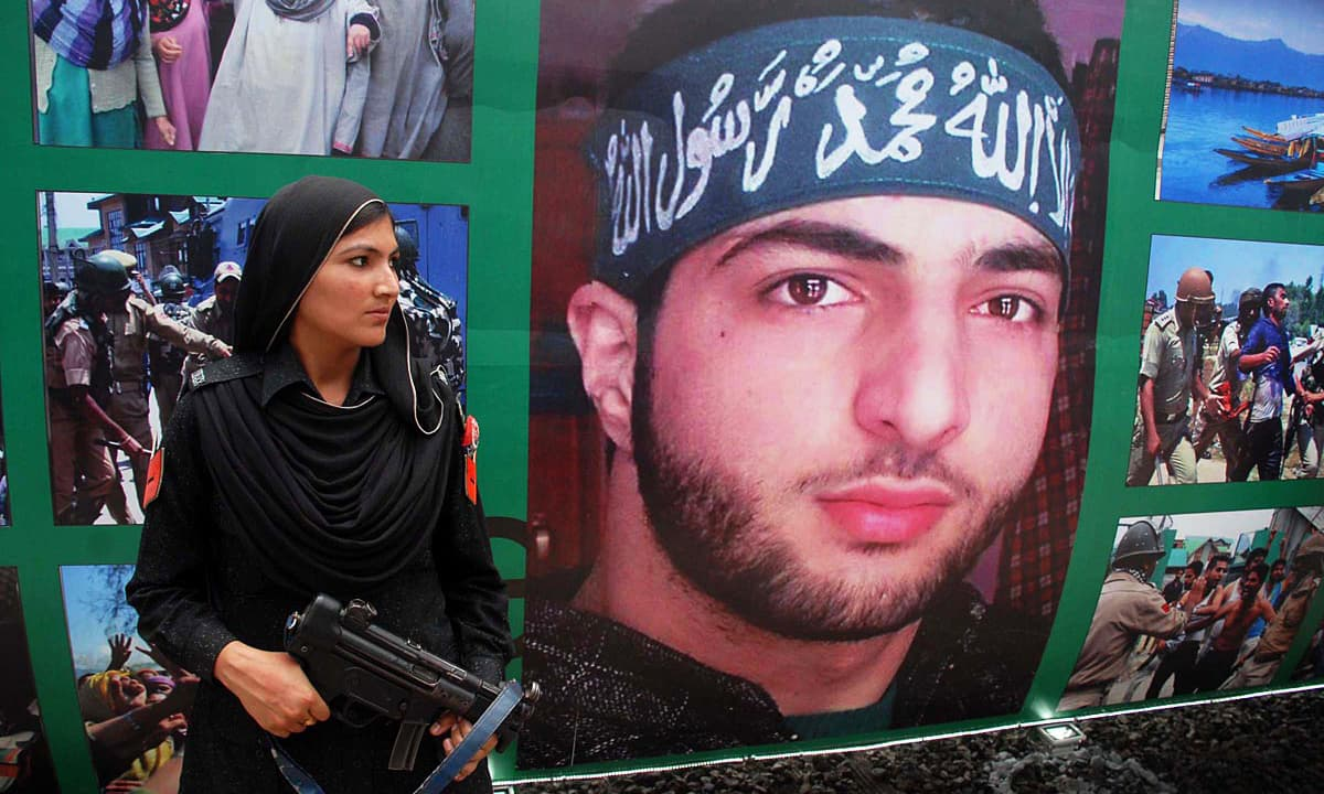 Police woman stands in front of a picture of Burhan Wani during inauguration ceremony of Azadi Train. Online