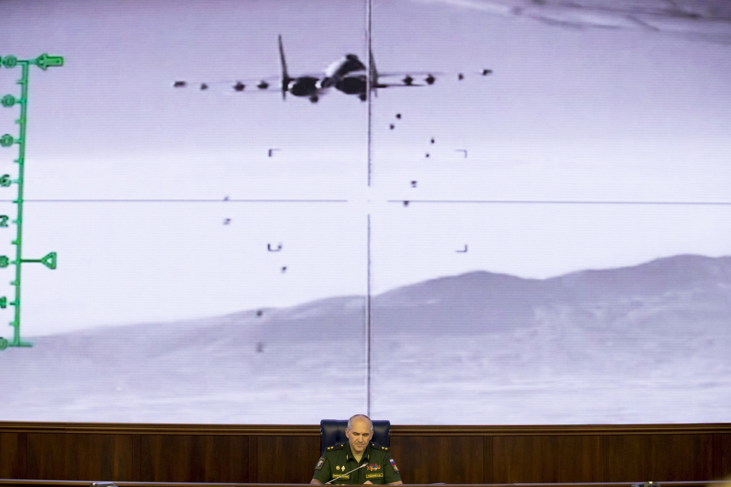 Lt.-Gen. Sergei Rudskoi of the Russian Military General Staff speaks to the media, as a video released by the Russian Defense Ministry shows a Russian warplane unloads its weapons over target on screen at a Russian Defense Ministry building in Moscow, Russia, Wednesday, Aug. 10, 2016. Rudskoi said that fighting in Aleppo will cease for three hours daily to allow humanitarian aid deliveries. (AP Photo/Ivan Sekretarev)