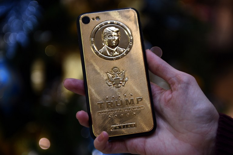 An employee of Caviar Phones, a Russian-Italian company specializing in smartphone customization, displays a special gold-plated iPhone 7 smartphone bearing the likeness of US President-elect Donald Trump - at a minimum price of 197 000 rubles (2755 euros / 2971 dollars) - in the company's boutique outside Moscow on November 14, 2016. / AFP PHOTO / Vasily MAXIMOV