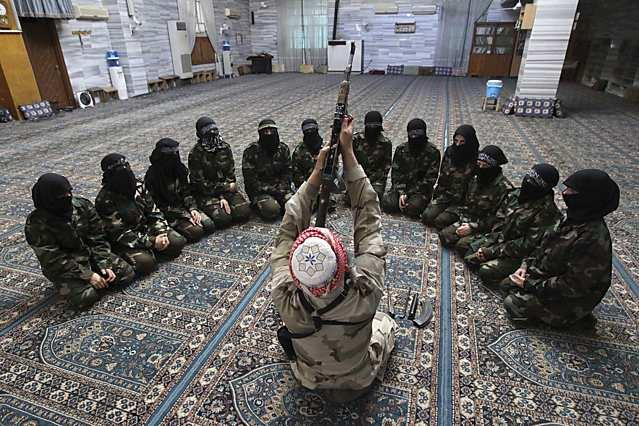 Abu al-Taib, the leader of Ahbab Al-Mustafa Battalion, demonstrates to female members as he holds a gun during a military training in a mosque in the Seif El Dawla neighbourhood in Aleppo in this June 24, 2013 file photograph. The civil war that has unfolded in Syria over the past two and a half years has killed more than 100,000 people and driven millions from their homes. Now, in the wake of last week's chemical weapons attack near Damascus, the world is waiting to see what action Western powers will take and what impact this will have on the Middle Eastern nation and the rest of the volatile region. REUTERS/Muzaffar Salman/Files (SYRIA - Tags: CONFLICT CIVIL UNREST MILITARY) ATTENTION EDITORS: PICTURE 34 OF 40 FOR PACKAGE 'SYRIA - A DESCENT INTO CHAOS.' SEARCH 'SYRIA TIMELINE' FOR ALL IMAGES